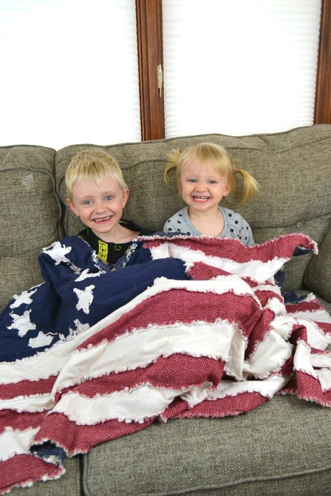 kids sitting with a flag rag quilt