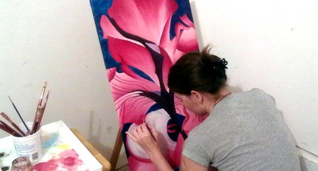 Heather working on a large painting of a flower.