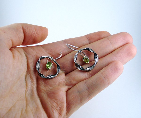mitsuro peridot earrings held in a hand