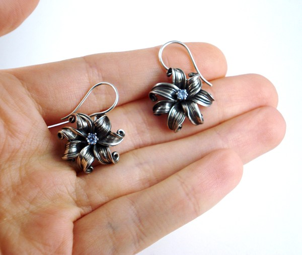 mitsuro flower earrings being held