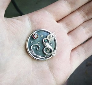 Finished Hawaii Moon Rabbit in sterling silver with a garnet and emerald