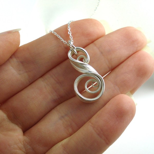swirl pendant held in a hand
