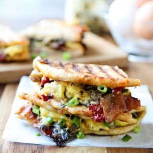 Breakfast Panini | Take your breakfast to the next level! Sun-Dried tomato pita bread, pesto, three kinds of cheese, scrambled eggs, bacon, sausage, roasted red peppers and scallions. A delicious and hearty breakfast sandwich that will keep you going all day. Ready in less than 30 minutes!| heavenlyhomecooking.com