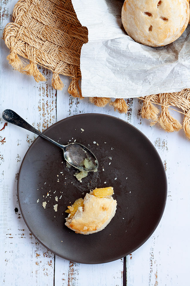 Overhead photo of a half-eaten pie sitting on a plate with spoon.