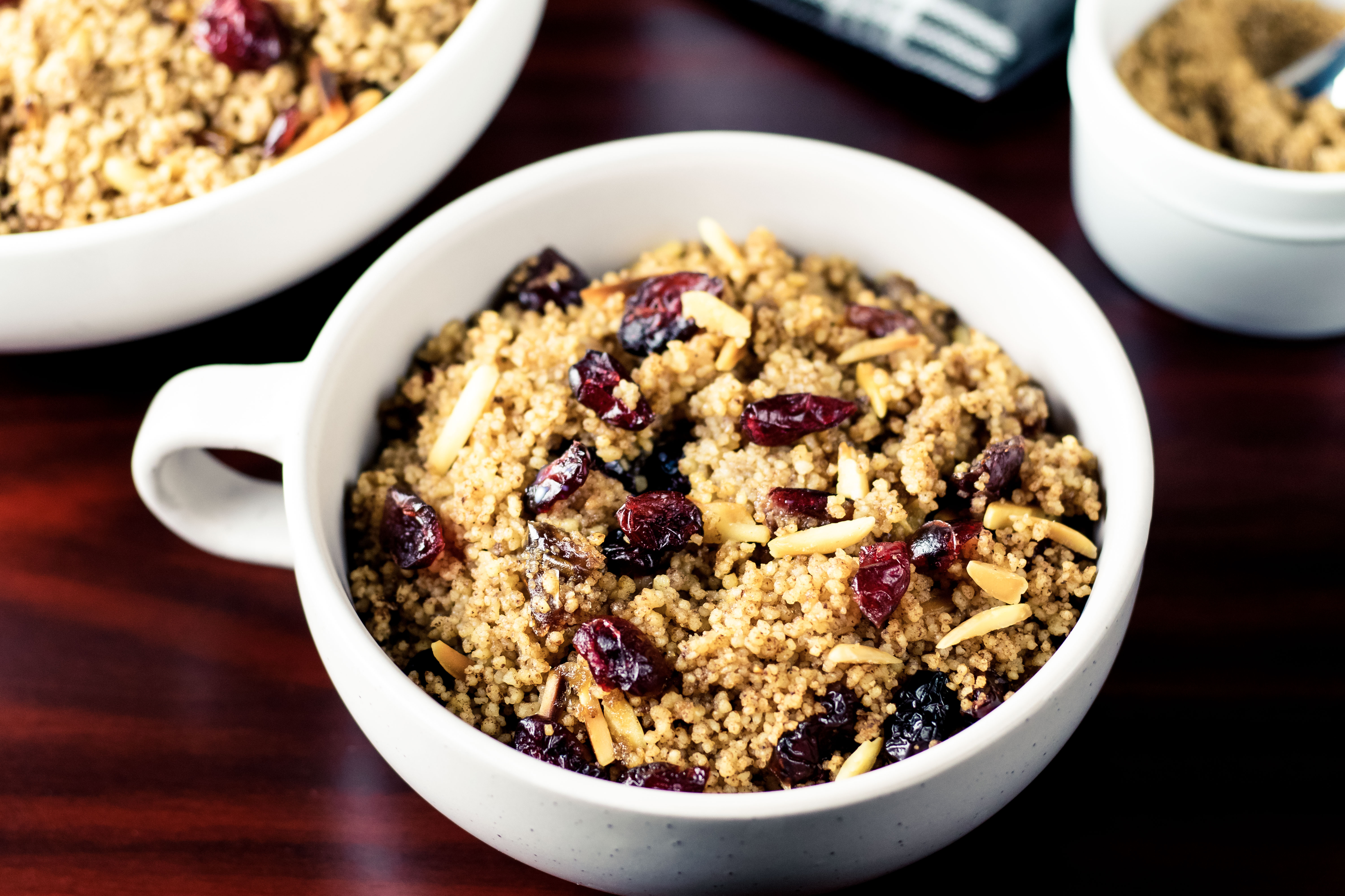 Close up of a bowl of couscous with dried fruit and slivered almonds. A big serving bowl of couscous, and ramekin of brown sugar are sitting in the background.