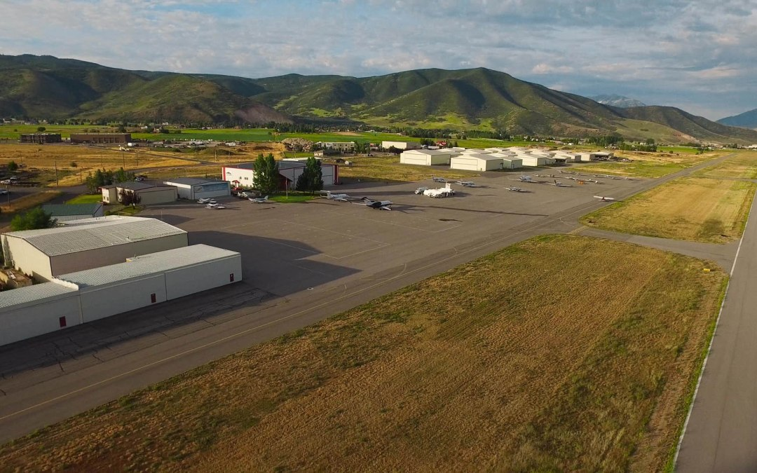 Aerial shot of Heber Airport runway, ramp, and hangars with mountains in the background
