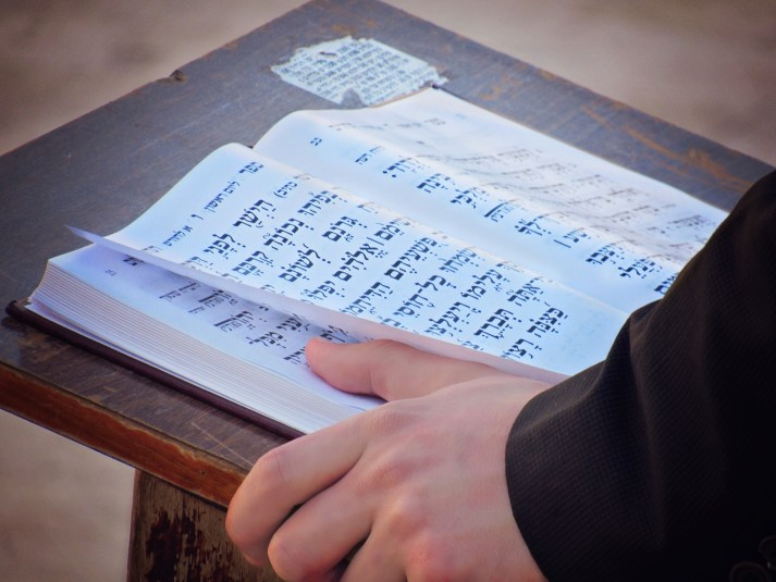 Hebrew Scriptures on stand with hand holding the book