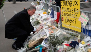 "New York city mayor Bill de Blasio lays a wreath of flowers at the kosher grocery where Amedy Coulibaly killed four people in a terror attack, in Paris, Tuesday Jan. 20, 2015. Brothers, Said and Cherif Kouachi and their friend, Amedy Coulibaly, killed 17 people at the satirical newspaper Charlie Hebdo, a kosher grocery and elsewhere last week. The yellow poster reads: ""Brave police officers and gendarmes, Thank you."""