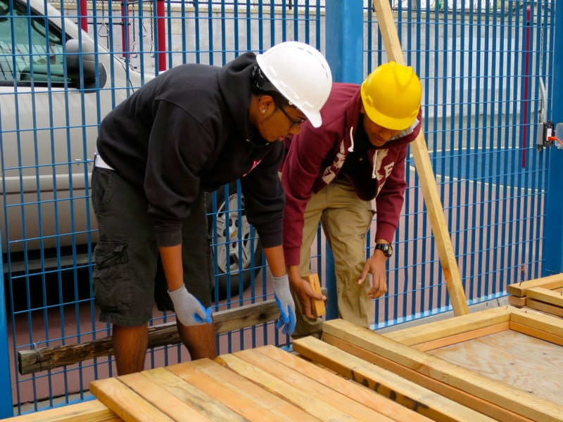 Juniors at the High School for Construction Trades, Engineering and Architecture prepare to erect walls for small houses they will build on the school grounds.