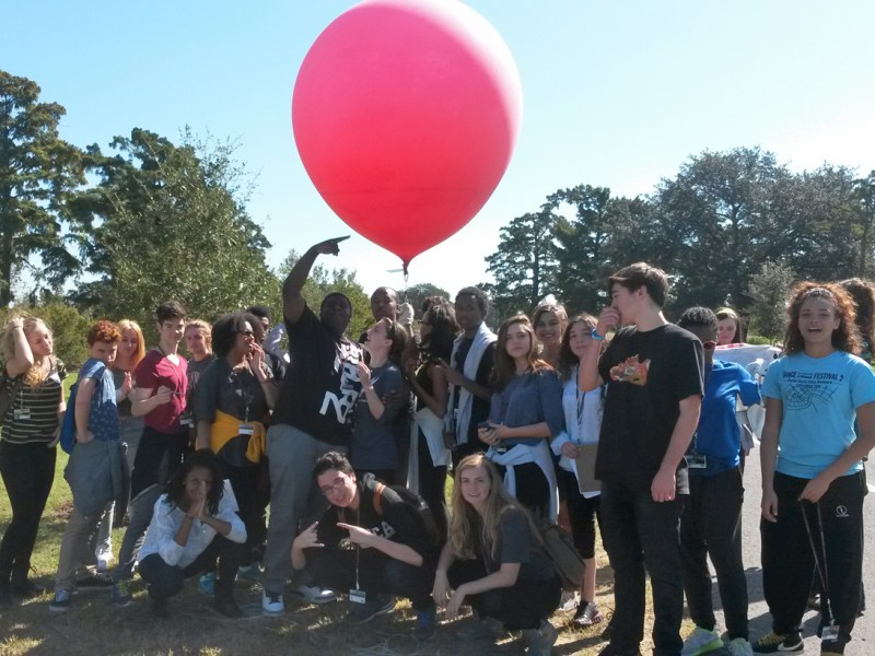 Students in Travis Haas's class at the New Orleans Center for Creative Arts, with one of the red helium balloons they use to monitor pollution and the progress of wetlands recovery