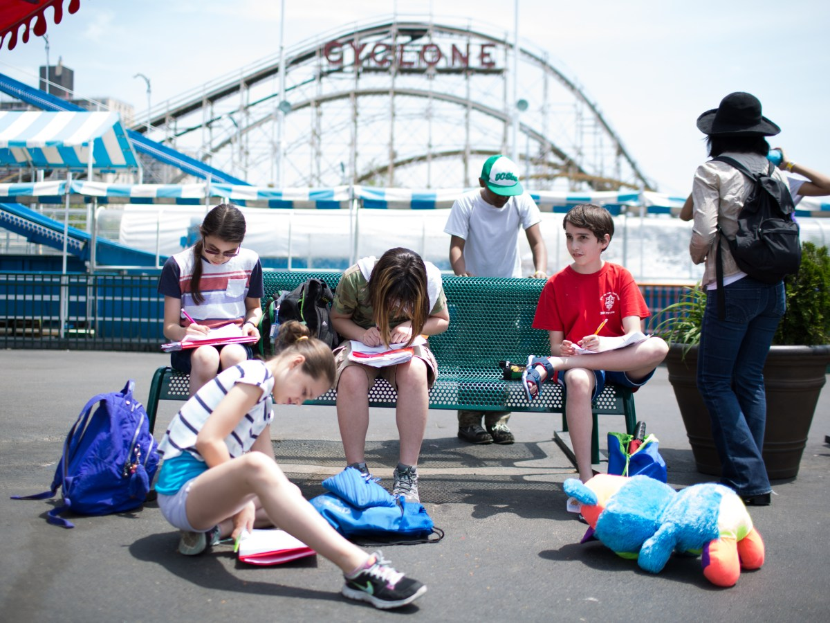 Students Mia Ramsey, 11, left, Ella Reyl, 12, Thea Jones, 12, Seth Samuel, 12, and Etai Kurtzman, 12, fill out game analysis worksheets at Coney Island in Brooklyn, NY May 28, 2015. The group of students from Quest to Learn School took the day trip to Coney Island to analyze user experience on games and rides at Luna Park as part of their late-spring school curriculum.