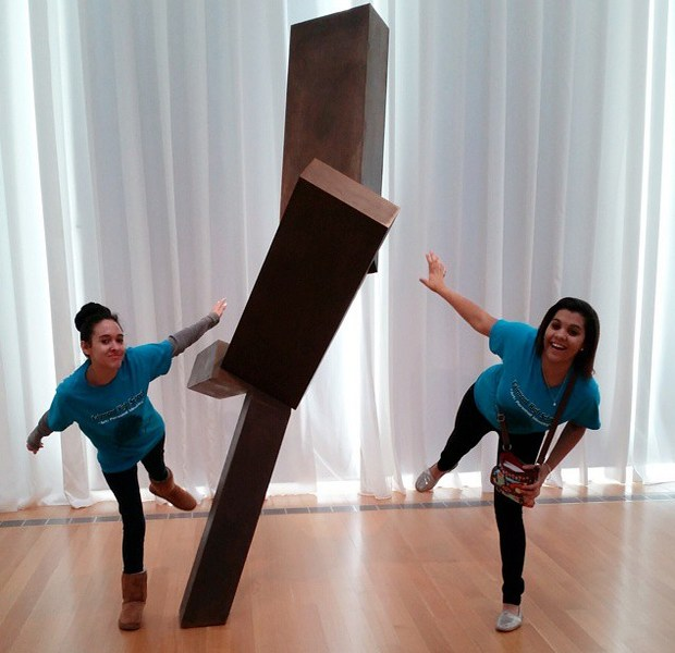 """Kelsey Hunt, left, and Harley Graham, right, students from Fairmont High School in Fairmont, North Carolina, pose with Joel Shapiro's 'Untitled' as part of a virtual exhibit they created during a """"flipped field trip"""" at the North Carolina Museum of Art."""