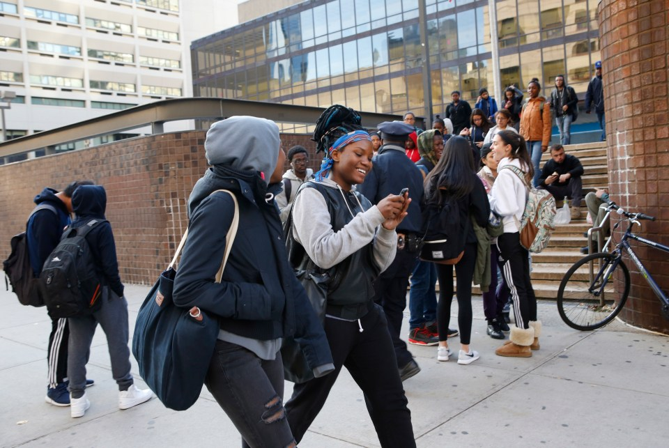Students chat as they leave Martin Luther King Jr. High School Tuesday, Nov. 17, 2015, in New York.