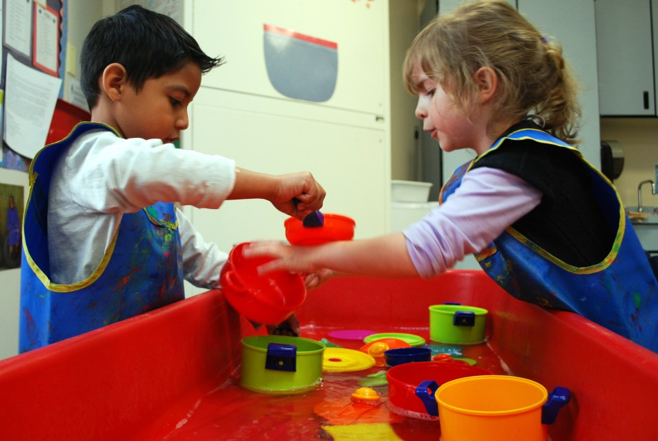 Preschool students at Kruse Elementary School in the Poudre School District in Colorado play at the water table during choice time.