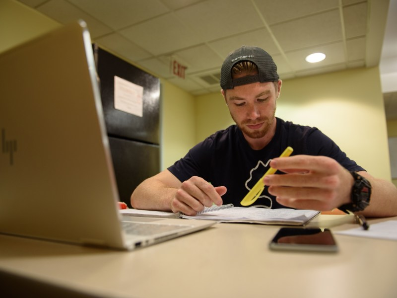 """Josh Caouette, a graduate student at Simmons College, crams for a test. Caouette is resigned to the cost of his degree. """"If it's helping others, that's fine by me. I mean, I have to do it either way."""""""