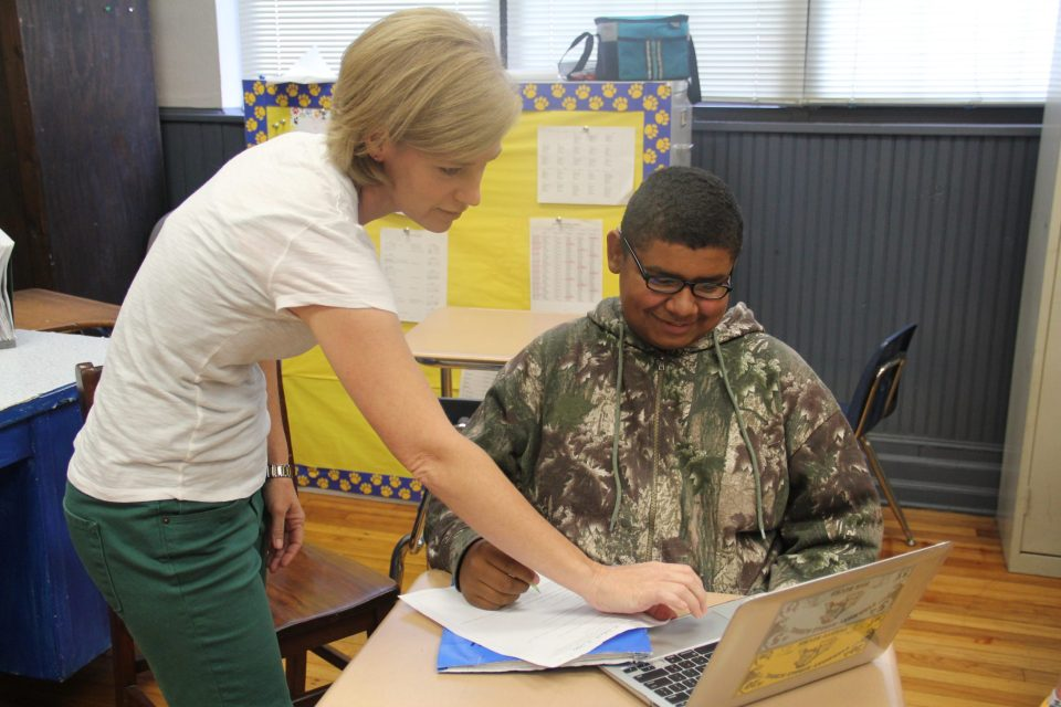 A teacher helps a student who is otherwise working independently on his laptop.