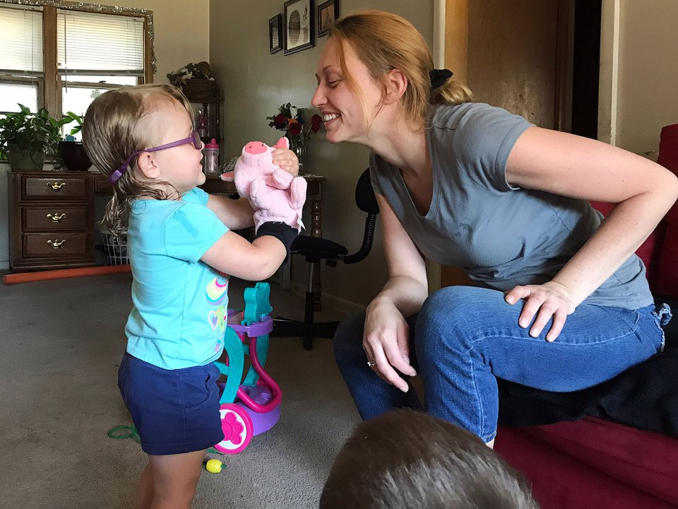 Tiffany McNitt, right, leans in to interact with the pig puppet her daughter Alexis, 2, is showing her. McNitt wants to find a child care option that will help her children prepare for kindergarten. Lillian Mongeau/The Hechinger Report