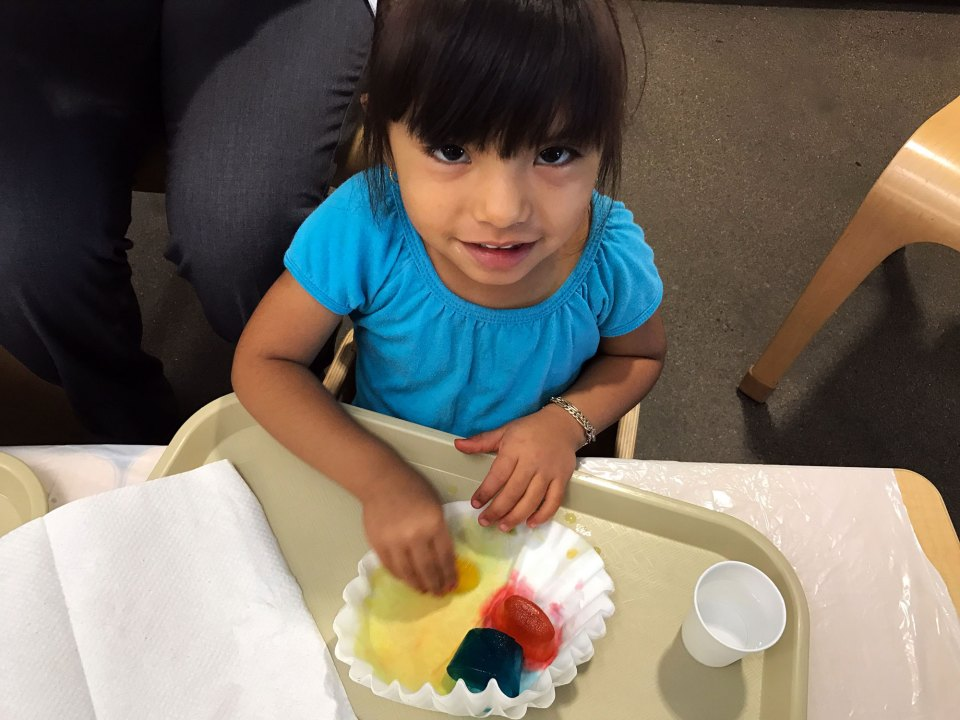 Shailey Ortiz pauses in the midst of completing an art project in the toddler room at Educare Arizona in Phoenix. Lillian Mongeau/The Hechinger Report