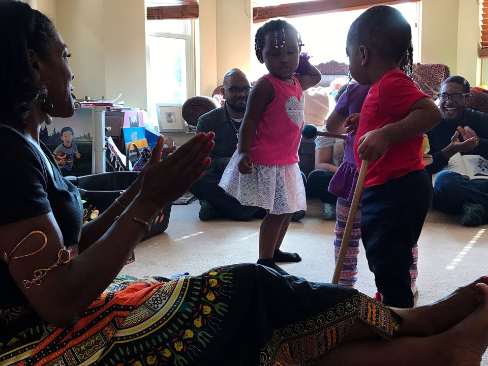 Maikko, 2, in pink, Terrance, 1, in red, and Nylah, behind Terrance, dance as their child care provider, Lorna Parks, foreground, claps during a visit by staffers from Detroit's African-American History Museum.