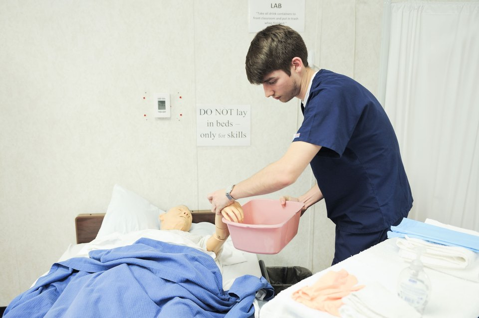 "Brandon Harris, 19, tests the water temperature before giving a ""rag bath"" to a mannequin in a class at West Georgia Technical College to become a nurses' aide."