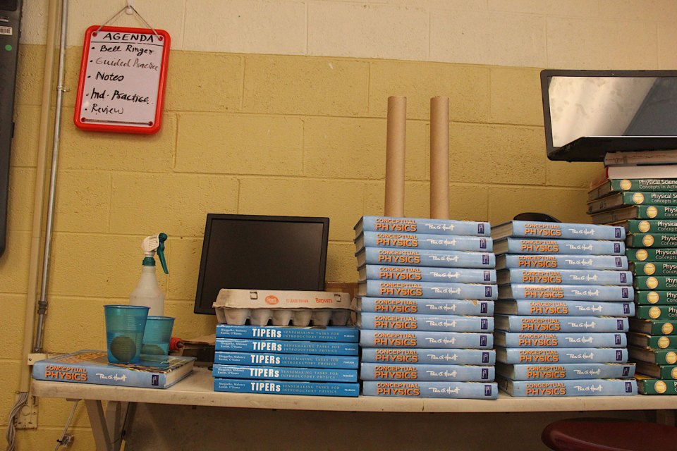 A stack of old physics textbooks sits in a classroom at Holmes County Central High School. The Global Teaching Project purchased new textbook for students taking AP physics this year.