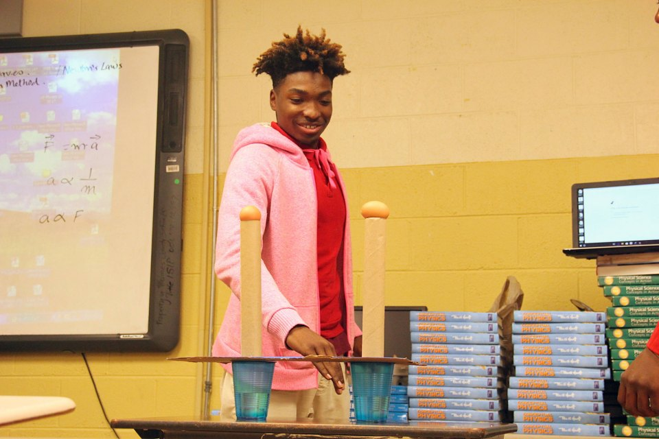 Student Jaylen Dennis sets up an experiment to test one of Newton's Laws.