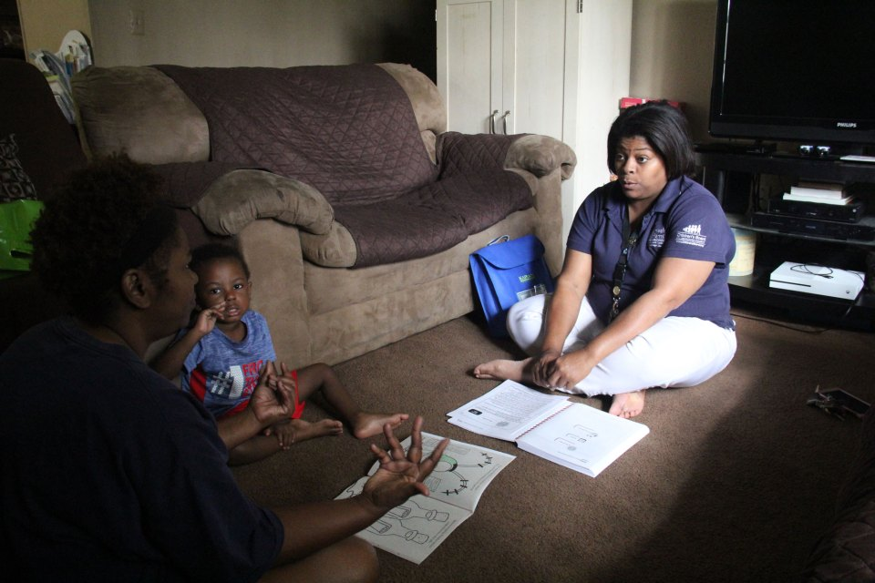 Yamika McCalpine, a home visitor with Health Families, sits on the floor in Monica Gadson's house.