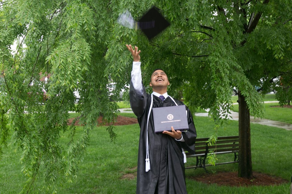 Jacob Maldonado, DACA student, tosses his mortarboard in the air after graduating from Trevecca Nazarene University.