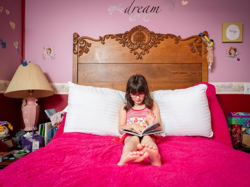Tessa, 7, of Lafayette, Indiana, reads a book in her bright pink bedroom.