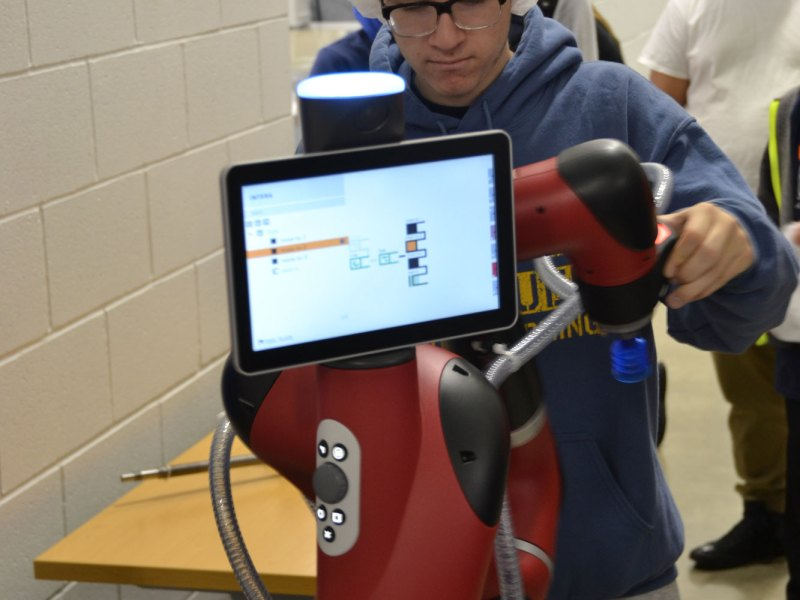 """Matthew Porter, a student at Craig High School, inspects a """"collaborative"""" robot at Prent Corporation, in Janesville, Wisconsin."""