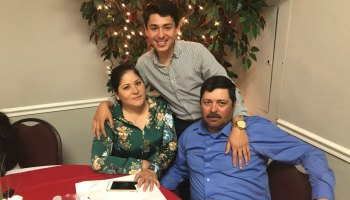 Freshman Arnaldo Gonzalez with his parents after the College Assistance Migrant Program celebration dinner in April.