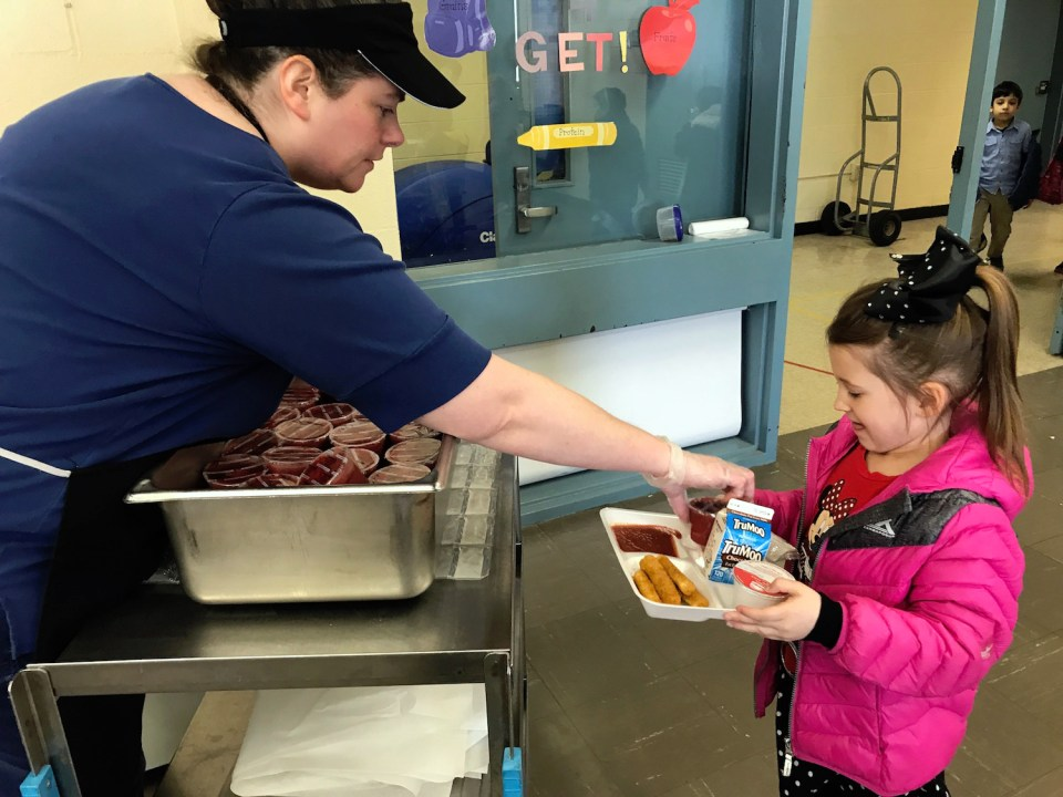 Avery Geddes, 6, is served a fruit snack for dessert during lunch at Main Dunstable Elementary School in Nashua, New Hampshire. The social benefits of eating lunch at school have been a huge unexpected benefit of full-day kindergarten said principal, Kelley Paradis.