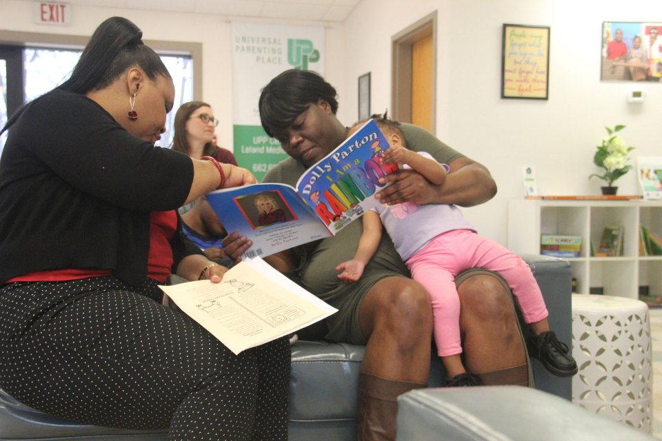 Jennifer Townsend reads to two of her children before a parenting class in the Leland Medical Clinic's parent center.