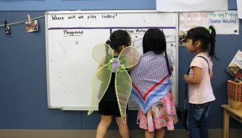 Students play dress-up and draw on a whiteboard in a Christopher House preschool class.