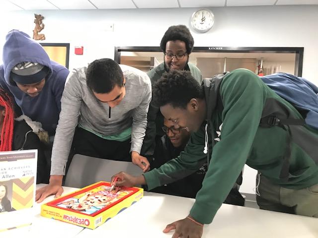 Adley Nyakora, a freshman at Minnesota State University, Mankato, plays Operation, while Cornelius Bright, Elijah Calderon-Pitchford, Aburrahman Guantai, and Jordan Headley look on.