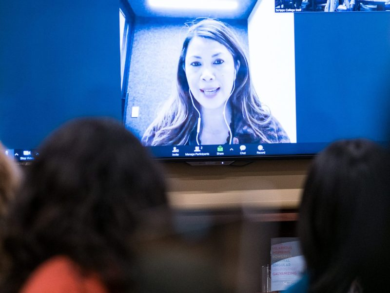 Students partake in online education, attending a zoom lecture projected in the big screen