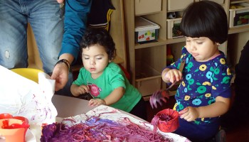 Parents work with children under the guidance of a home visitor in Gads Hill's Early Head Start Home Visiting program.