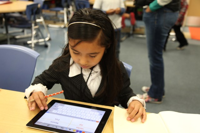 A first-grader at Maywood Elementary, in Maywood, Calif., uses her iPad to complete a chart separating nouns and verbs. (Photo: Brenda Iasevoli)