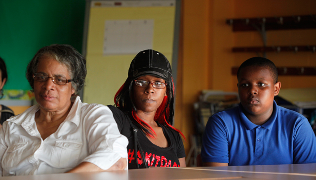 D'Andre's paternal grandmother, Jean, and his mother, Taneka, sit with him as his social studies teacher gives an overview of the year ahead at back-to-school night. D'Andre has lived with Jean since he was 3, and Taneka has recently become more active in his life. (Amanda Brown / NJ Spotlight)