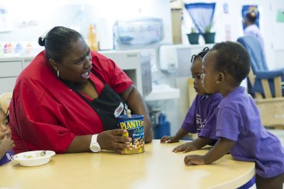 Lashane Bates, an assistant teacher, works in a classroom of 1- to 2-year-olds at Educare, which accepts children as young as six weeks. Research shows that the younger children are, the more effective interventions will be. (Kim Palmer / Hechinger Report)