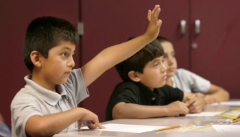 Emmanuel Angeles, raises his hand to be called on while doing a worksheet in an English Language Learner summer school class at the Cordova Villa Elementary School in Rancho Cordova, Calif. (AP Photo/Rich Pedroncelli)