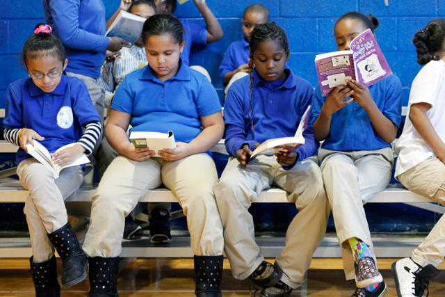 In the Quitman gym, students look at the new books they received as a reward for the school's academic progress. (Amanda Brown / NJ Spotlight)