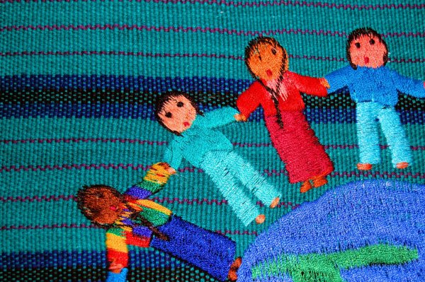 Sewn images of diverse people holding hands across a globe