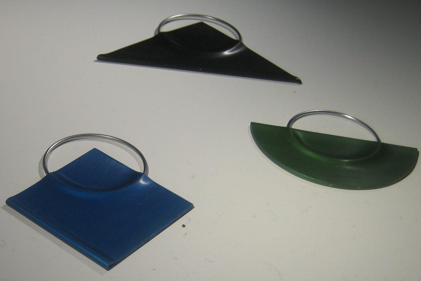 Anneke van Bergen, drie broches, 1979. Sieradenpresentatie lockers, Collectie Centraal Museum, 21674, 21675, 21676, metaal