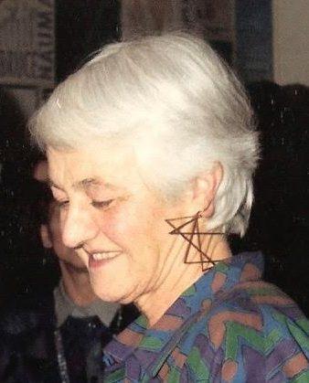 Riet Neerincx draagt oorsieraad van Nicolaas van Beek tijdens haar afscheid van het Gemeentemuseum Arnhem, 19 december 1986, metaal