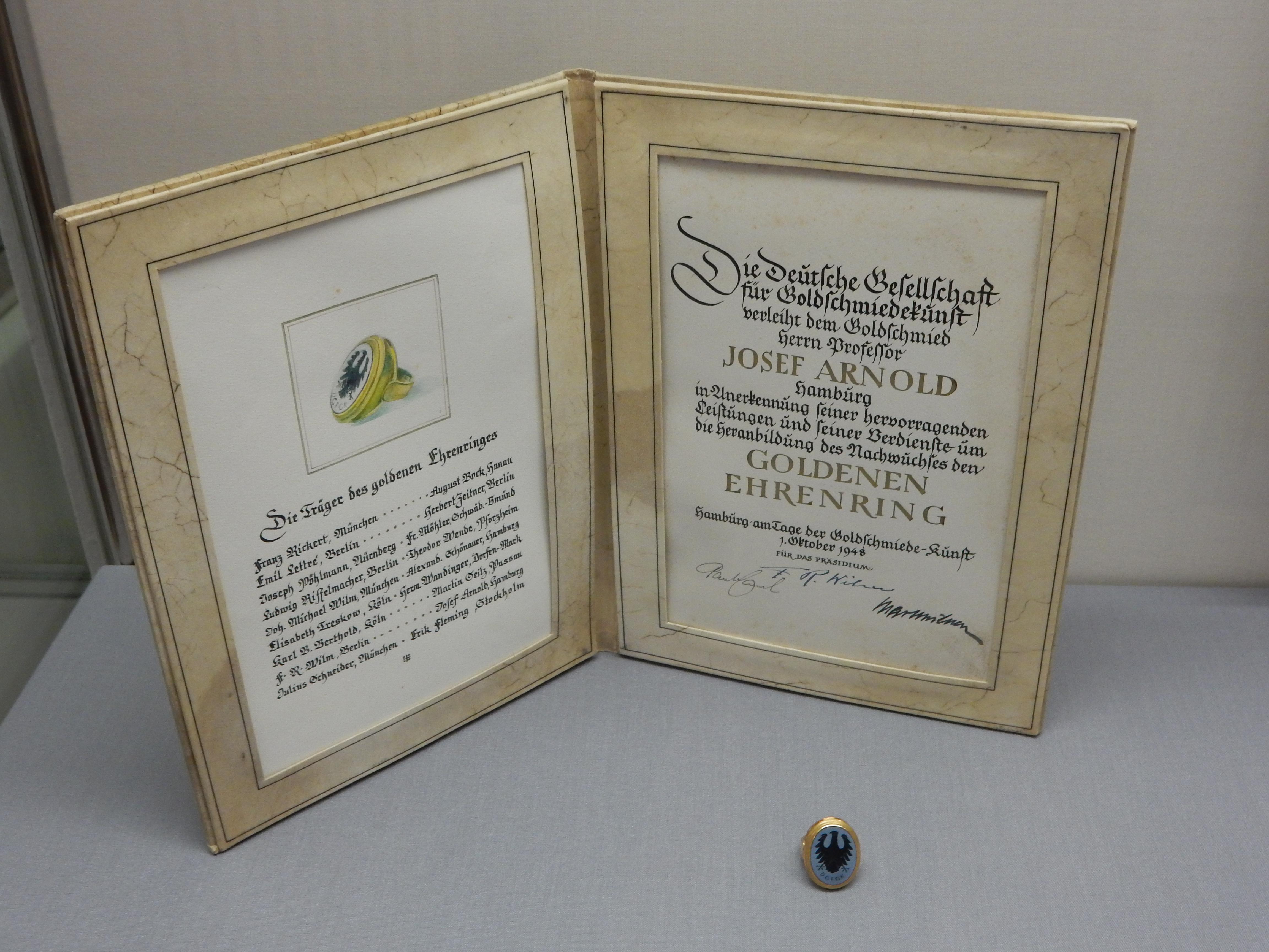 Oorkonde Goldener Ehrenring voor Josef Arnold. Deutsches Goldschmiedehaus. Foto Coert Peter Krabbe, mei 2019, papier, goud