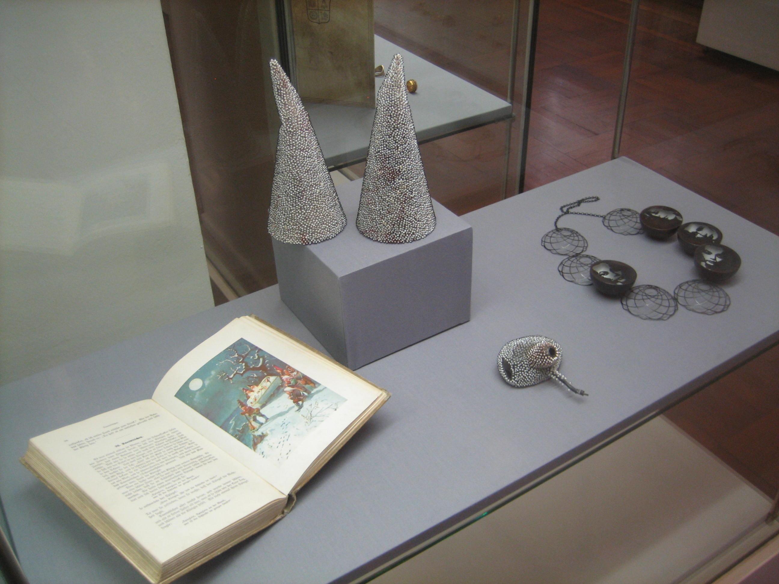 Sam-Tho Duong, objecten, 2014, Look, broche, 2011, Vera Siemund, halssieraad, 2010. Deutsches Goldschmiedehaus, vitrine, email, boek, papier, zoetwaterparel, kunststof, zilver