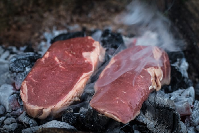 two dirty steaks cooking on the embers of a campfire