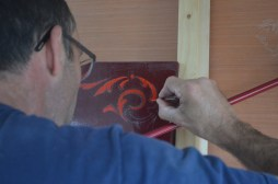 Ash paints steady-handed scrolls in the corners of our signboards
