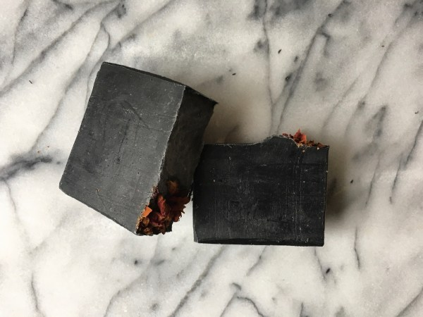 2 bars of Persephone charcoal soap, unwrapped, on a marble background